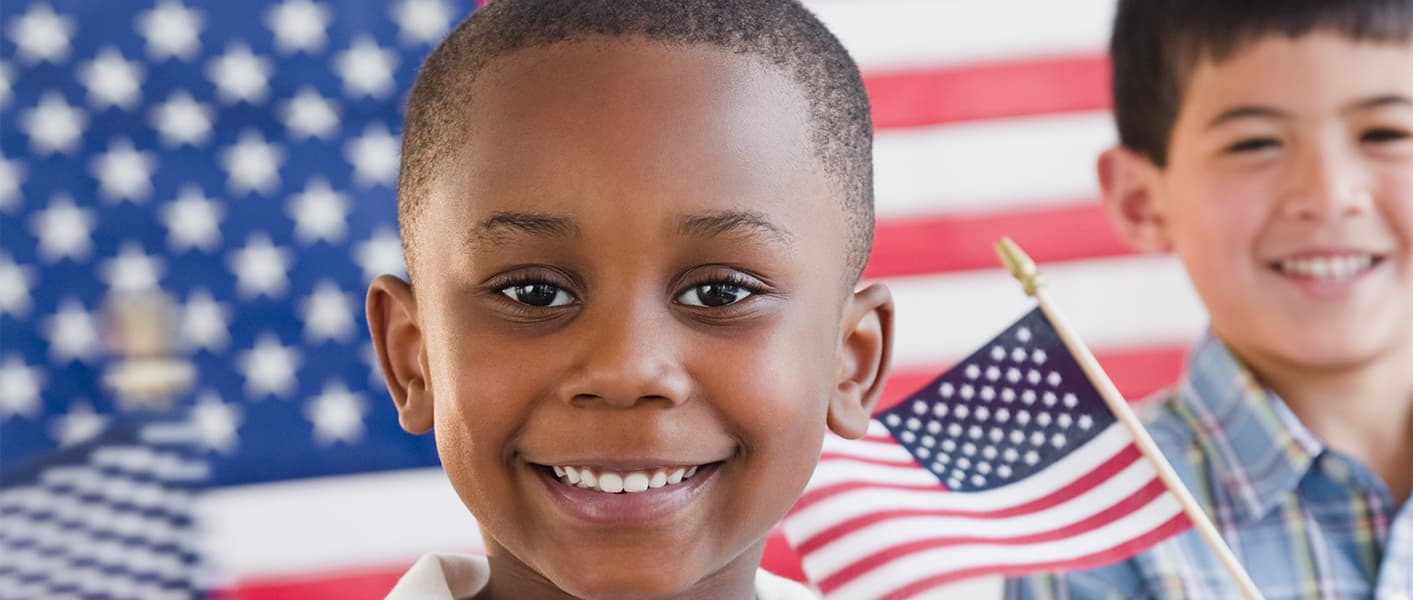 boy standing in front of US flags