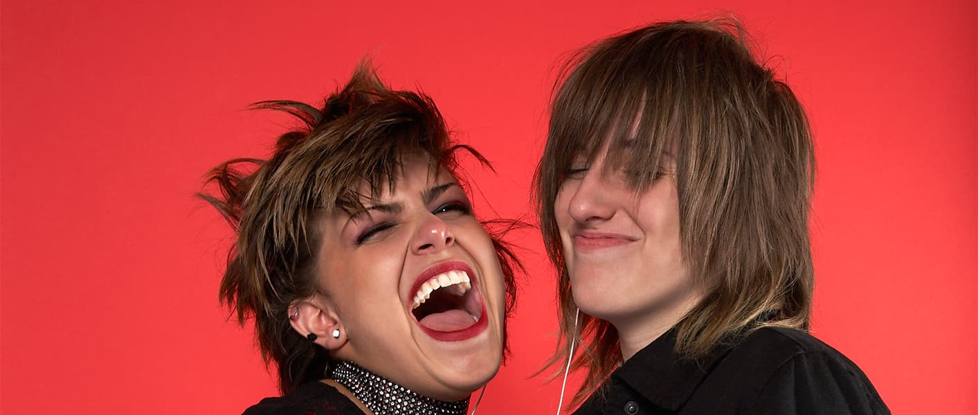 teens laughing behind red wall