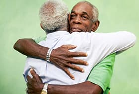 Two older men hugging