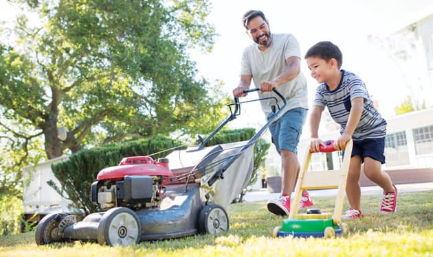 man and kid cutting grass